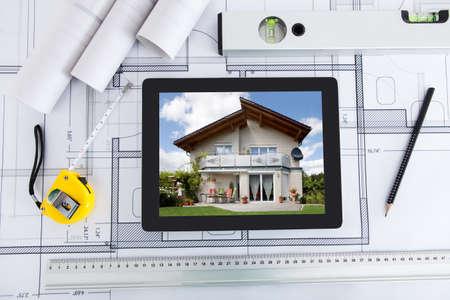 Maison affiché sur l'écran de la tablette numérique avec les outils de l'architecte sur plan Banque d'images - 27954234