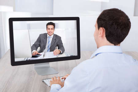 conferencing: Rear view of businessman video conferencing with coworker on desktop PC at office desk
