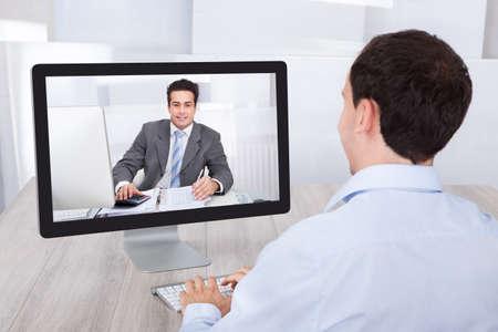 Vista trasera del hombre de negocios de videoconferencia con un compañero de trabajo en la PC de escritorio en escritorio de oficina Foto de archivo - 27954252