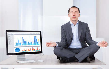 Full length of businessman mediating by computer on desk in office photo