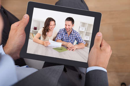 watching movie: High angle view of businessman watching movie on digital tablet in office