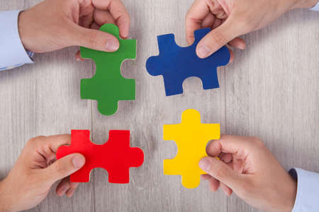 Cropped image of businesspeople joining multicolored puzzle pieces at desk in office photo
