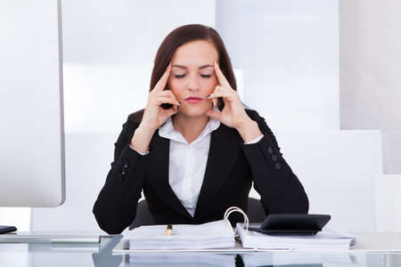 tensed: Tensed young businesswoman calculating tax at desk in office