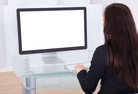 Achteraanzicht van zakenvrouw met behulp van de computer op het bureau in het kantoor