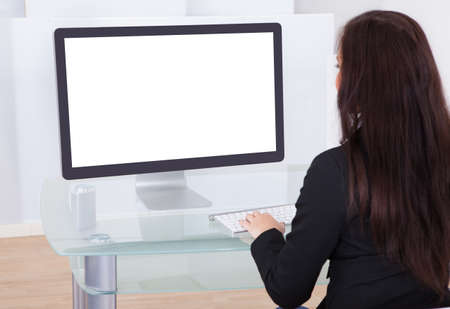 Rear view of businesswoman using computer at desk in office photo