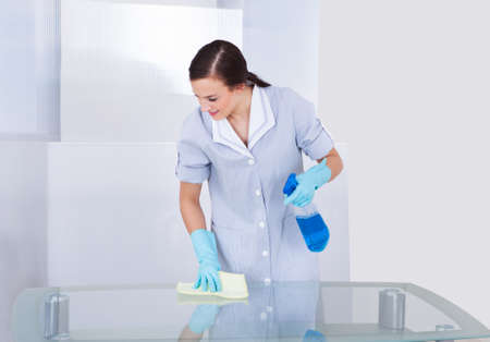 Portrait of happy young maid cleaning glass table at home