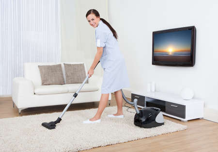 vacuum: Full length portrait of young maid cleaning carpet with vacuum cleaner at home