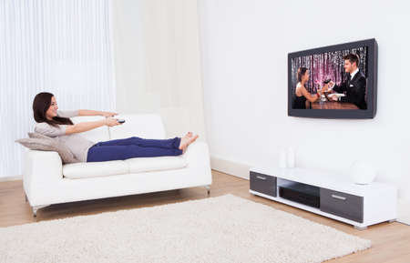 Full length of young woman watching TV while relaxing on sofa at home Stock Photo