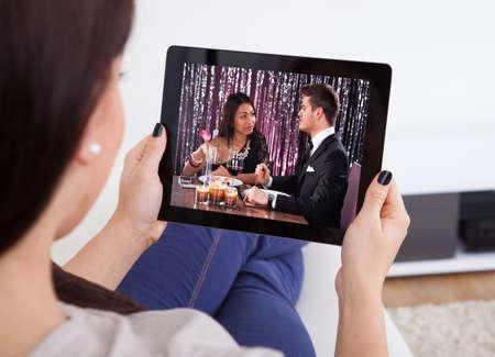 viewing: Immagine ritagliata di giovane donna che guarda tablet a casa