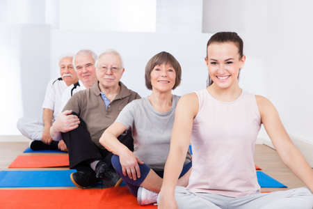 Portrait of smiling trainer and senior customers sitting together in yoga class photo