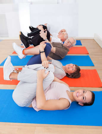 High angle view of trainer with senior customers exercising on mats at gym photo