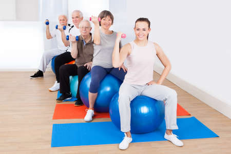 Portrait of trainer and senior customers using hand weights while sitting on fitness balls at gym photo