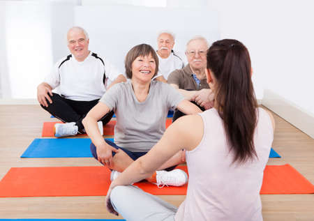 five people: Rear view of female trainer training senior customers on floor in yoga class