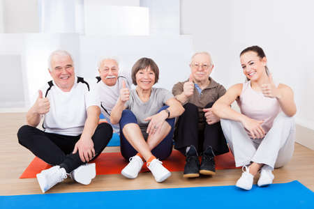Portrait of confident trainer with senior customers sitting on floor at gym photo