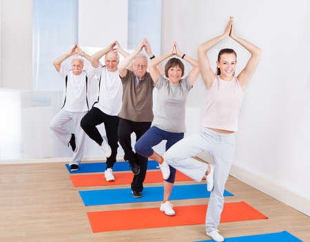 tree position: Full length portrait of trainer and senior customers practicing yoga in tree position at gym Stock Photo