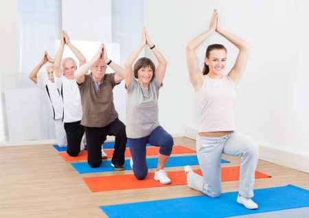 Full length portrait of trainer and senior customers practicing yoga at gym photo