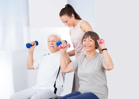 Young female trainer assisting senior couple with dumbbells at healthclub photo
