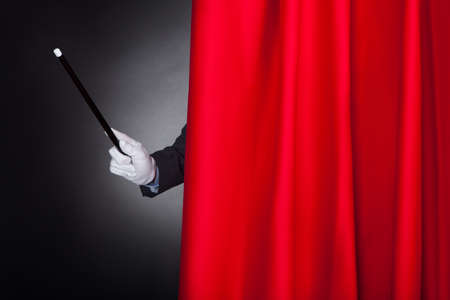 Cropped image of magician holding wand behind stage curtain photo