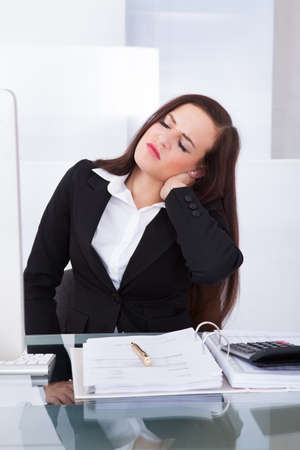 Young female tax consultant suffering from neck pain sitting at desk in office photo