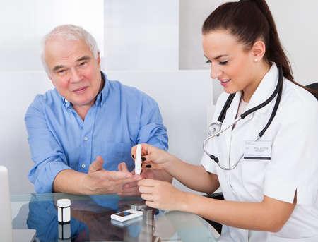 Female doctor using lancelet on senior man at desk in clinic