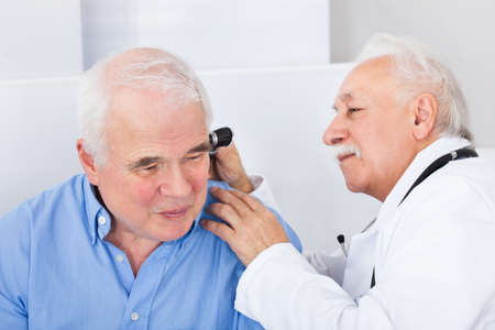 Smiling male doctor examining senior mans ear with otoscope in clinic