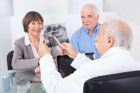 Male dentist explaining dental x-ray to senior couple in clinic photo