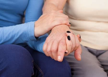 Midsection closeup of female caregiver consoling senior woman photo