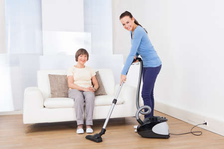 caretaker: Portrait of caretaker cleaning floor with vacuum cleaner while senior woman sitting on sofa at nursing home