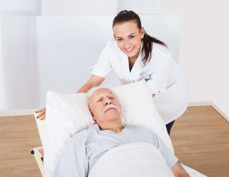 Portrait of happy female doctor with senior man lying in bed at clinic photo