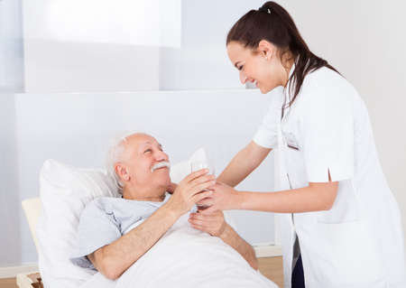doctor giving glass: Happy female doctor giving glass of water to senior man in hospital Stock Photo