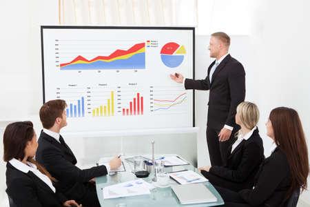financial graph: Businessman explaining project to colleagues in conference meeting at office