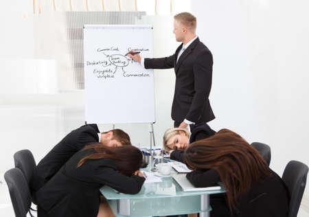 ビジネスマンおよび彼の同僚がプレゼンテーション中に眠っています。