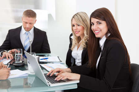 Portrait of smiling businesswoman sitting with colleagues in meeting at office photo