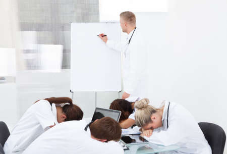 男性医師の診療所で机で寝て疲れている同僚にプレゼンテーションを行う