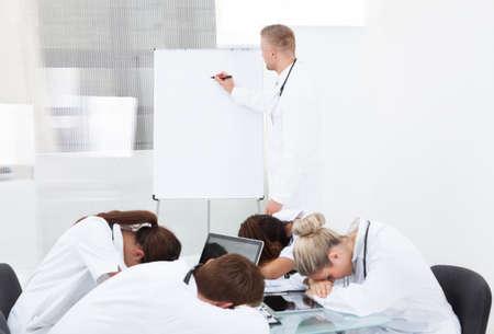 Muž lékař dává prezentace na unavené kolegy spí u stolu v klinice