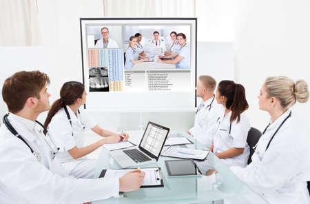 Team of doctors looking at projector screen in video conference meeting at hospital