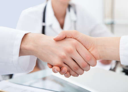 trusted: Cropped image of doctors shaking hands at desk in clinic