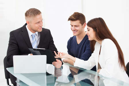 financial advice: Smiling young couple discussing with financial advisor at office desk Stock Photo