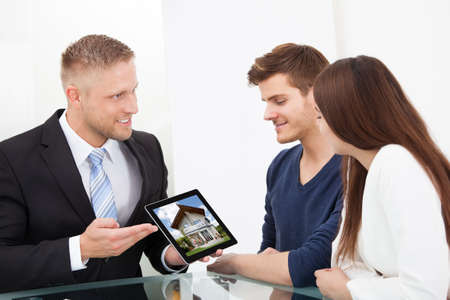 Businessman showing photo of a new home to couple on tablet at office desk