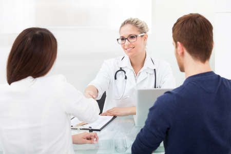 Female doctor shaking hands with couple at desk in clinic photo