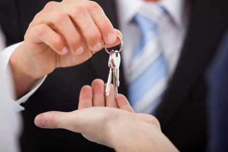 Bijgesneden afbeelding van vastgoedmakelaar geven huissleutels aan de mens in het kantoor Stockfoto