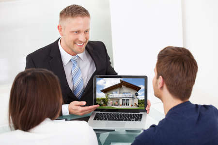 Smiling advisor showing house picture to couple on laptop at office desk photo