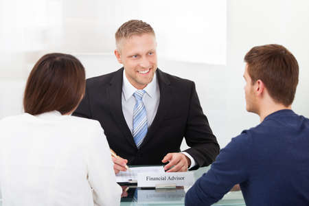 financial advisors: Rear view of young couple consulting financial advisor at office desk