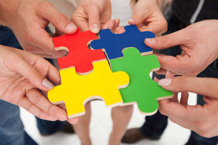 Cropped image of businesspeople joining puzzle pieces in office photo