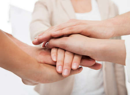 stacking: Cropped image of businesspeople stacking hands in office