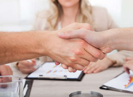 trusted: Cropped image of businessmen shaking hands at desk in office