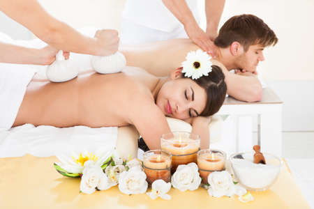Cropped image of therapist massaging womans back with herbal compress stamps at spa