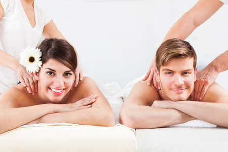 acupressure: Portrait of smiling young couple receiving massage at spa Stock Photo