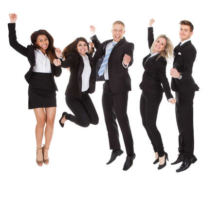 jump suit: Full length portrait of successful welldressed businesspeople with arms raised standing over white background Stock Photo