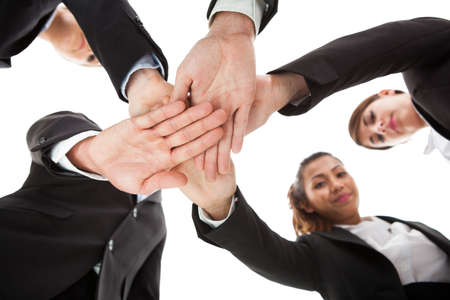 angle views: Low angle view of businesspeople stacking hands against white background